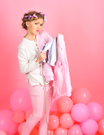 kleines Mädchen bügeln spielen. auf rosa Hintergrund Standard-Bild