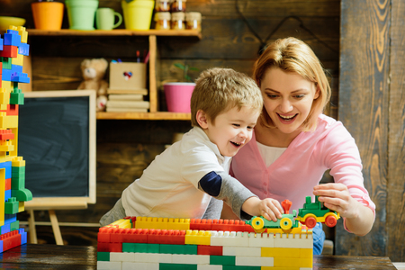 Motherhood concept. Blond mom and son play with plastic building blocks train. Excited preschooler playing with his smiling mother or kindergarten teacher.