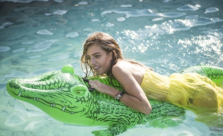 Sexy woman on sea with inflatable mattress. Relax in luxury swimming pool. Fashion crocodile leather and girl in water. Adventures of girl on crocodile. Summer vacation and travel to ocean, maldives. Stockfoto