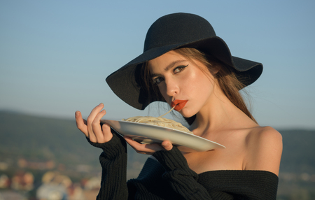 food and health. food of italian macaroni in hands of elegant woman in hat