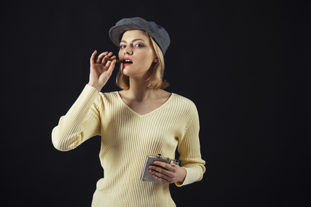 Woman on mysterious face wears kepi, dark background. Blonde lady looks like suspicious detective. Female logic concept. Girl thinking about investigation, holds flask and smoking cigar, copy space. Stock fotó