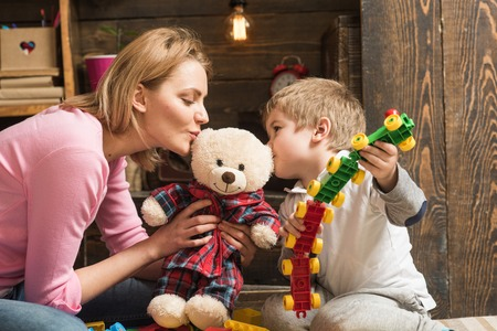 Kindness and education concept. Mother teaches son to be kind and friendly. Nursery wooden wall on background. Family play with teddy bear at home. Mom and child play with soft toy. 版權商用圖片