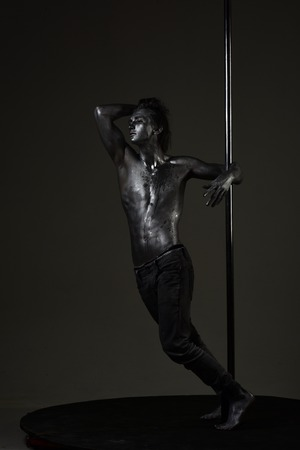 Pole dance man on pensive face stand near metallic pole, dark background. Guy with nude torso performing pole dancing moves on pole.