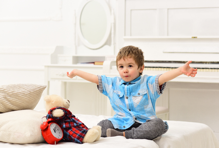 Child in bedroom telling fairytale for toy. Fairytale concept. Kid put plush bear near pillows and alarm clock, luxury interior background. Boy with favourite toy on bed, wishing sweet dreams.