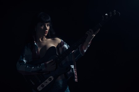 Sexy girl with sensual face and beautiful breasts on black background. Woman with make up holds electric guitar in dark room. Desire, beauty, style, fashion concept. Rock and roll music and drive. Standard-Bild