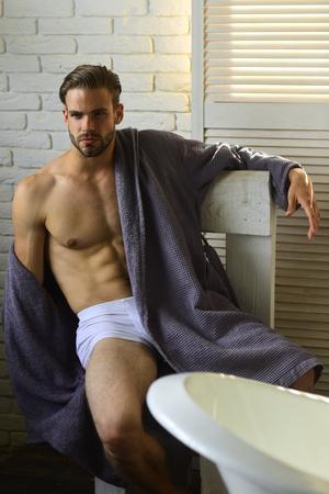 Fitness, bodycare, wellness. Man with fit body in underwear, bathrobe, fashion. Sexy macho with six pack, ab, torso in bathroom, fitness. Health, bodycare, hygiene. Fashion, home wear, underwear.