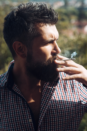 young bearded hipster with beard and moustache on serious face smoking cigarette outdoor. man smoking cigarette. unhealthy lifestyle and bad habit of guy with addiction. hairdresser and barbershop