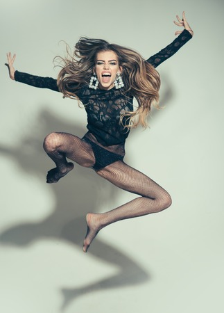 Lady on screaming face, enjoy freedom. Impudent lady looks attractive, sexy, light background. Sexy woman jump high in air. Girl in lace top and underwear, tights in black panties. Freedom concept. Фото со стока