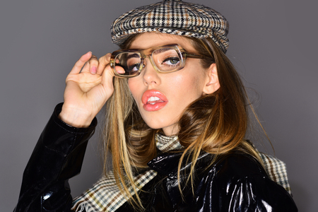 Woman on pensive face with make up wears checkered accessories and glasses for vision. Sexy lady in stylish outfit, close up. Accessories concept. Girl wears kepi, scarf and glasses, grey background.