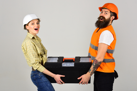 Repairman and girlfriend holding toolbox together, copy space. Smiling woman in helmet excited about renovation. Builders with toolbox, couple in love makes repair grey background. Renovation concept. Stock Photo