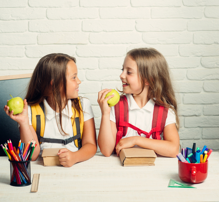 Back to school and home schooling. Little girls eat apple at lunch break. School time of girls. Friendship of small sisters in classroom at knowledge day. Happy school kids at lesson in september 1.