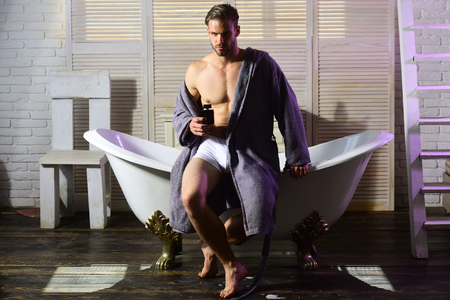 Man with perfume bottle in bathroom. Man with muscular torso in underwear and bathrobe on bath. Banque d'images