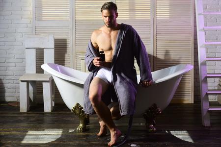 Man with perfume bottle in bathroom. Man with muscular torso in underwear and bathrobe on bath. Archivio Fotografico