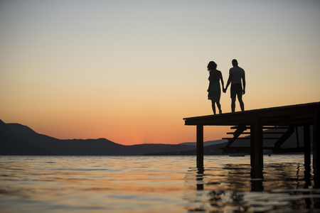 Silhouette of sensual couple stand on pier with sunset above sea surface on background. Couple in love on romantic date in evening at dock, copy space. Romance and love concept.