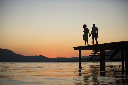 Silhouette de couple sensuel debout sur la jetée avec coucher de soleil au-dessus de la surface de la mer sur fond. Couple amoureux sur rendez-vous romantique en soirée au quai, espace copie. Concept de romance et d'amour.