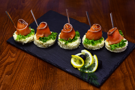 Cold appetizers, canape with red fish, wooden background. Canape with salad leaves, red fish, lemon and dill. Restaurant dish concept. Delicious snacks served in restaurant on black dishes. Archivio Fotografico