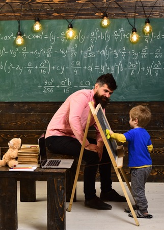 Tutor explaining math to little kid. Turned back boy wiping chalkboard with yellow cloth. Daddy sitting on the table while talking to the son.