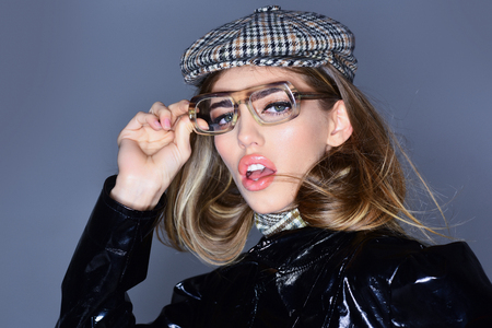Sexy lady in stylish outfit, close up. Woman on pensive face with make up wears checkered accessories and glasses for vision. Optics concept. Girl wears kepi, scarf and glasses, grey background.