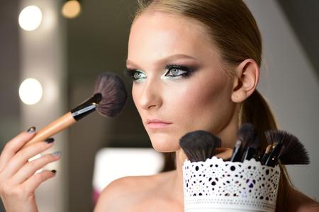 Beautiful woman face powder, and apply blush to cheekbones.