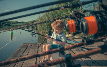 Adorable baby sit on river pier with fishing rod and fishing. Banco de Imagens