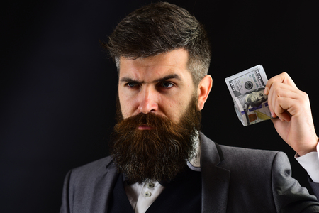 Businessman, man in formal wear with beard and mustache on serious face holds roll made out of dollar, money. Profit concept. Businessman in classic suit, close up, black background, copy space. Banque d'images - 99920134