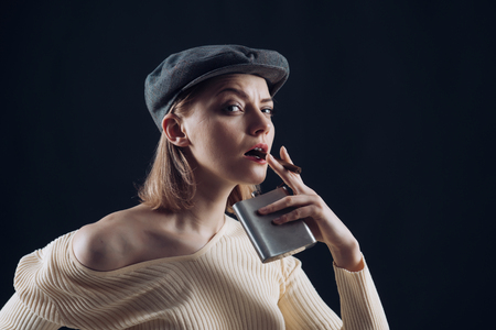 Blonde lady looks like suspicious detective. Detective concept. Girl thinking about investigation, holds flask and smoking cigar, copy space. Woman on mysterious face wears kepi, dark background. Stock fotó
