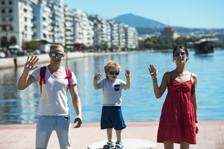 Mother and father and their child waving hands. Happy family spend time together, waving hands, sea and urban background. Parents with son stand on seafront. Family vacation concept.