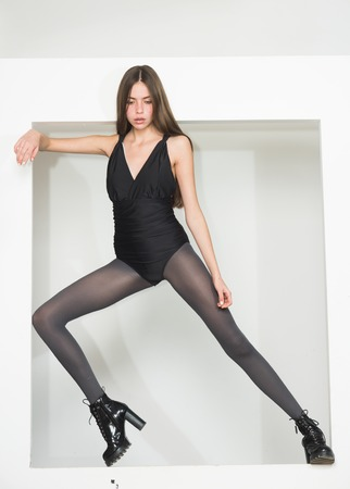 Fashionable lady with make up and skinny legs stand, white background. Lady slim wears black swimsuit and tights. Girl with long hair on mysterious face. Fashion and beauty concept.