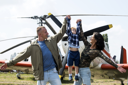 Happy family spend time together, on excursion, helicopter or plane on background, sunny day. Development and upbringing concept. Mother and father and their child walking in aviation museum outdoors.