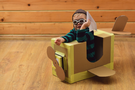 Kid, pilot school, innovation. Little boy child play in cardboard plane, childhood. Air mail delivery, aircraft construction. Pilot travel, airdrome, imagination. Dream, career, adventure, education. Stockfoto