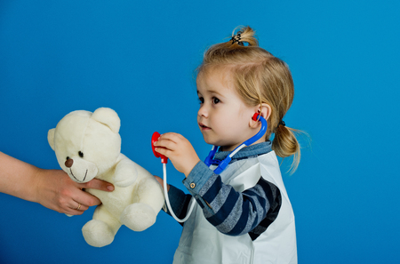 Health, healthcare, medicine. Boy doctor examine toy pet with stethoscope on blue background. Veterinary clinic game. Future profession concept. Child play veterinarian with teddy bear in mothers hand Stock Photo