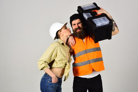 Housewife flirting with repairman with toolbox. Girl with helmet on kissing face near strong man with beard. Stock Photo