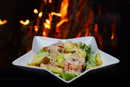 Caesar salad served in white plate in shape of star. Restaurant dish concept. Traditional dish in the restaurant - Caesar salad, fire on background.