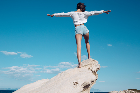 Girl enjoys freedom on windy day, put hands at sides. Lady stands on stone or reef in sea. Vacation and freedom concept. Woman enjoy view and feels free, blue sky background, rear view.