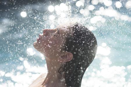 waterdruppels op het gezicht van een jonge vrouw. water baden in zwembad. Stockfoto