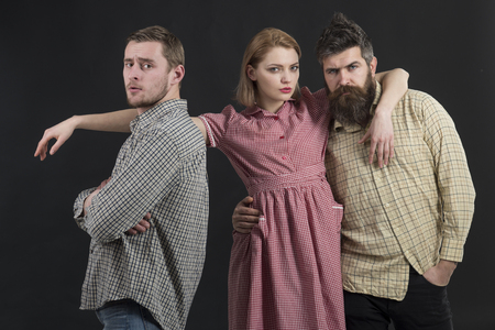 Love triangle concept. Men, woman on pensive faces, black background. Men in checkered clothes, retro style. Company of confident people, friends. Relations, communication, friendship, love, betrayal. Stock Photo