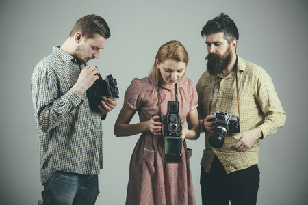 Men in checkered clothes, retro style. Company of busy photographers with old cameras, filming, working. Men and woman on pensive faces on grey background. Vintage photography concept. Stock Photo