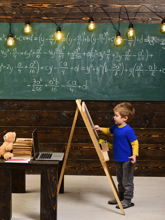 Little boy writing on chalkboard. Side view kid in front of green board with math equation. Smart little fellow studying math.
