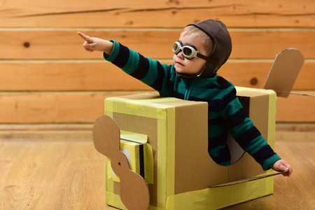 Kid, pilot school, innovation. Dream, career, adventure, education. Little boy child play in cardboard plane, childhood. Pilot travel, airdrome, imagination. Air mail delivery, aircraft construction. Stockfoto