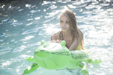 Summer vacation and travel to ocean, maldives. Fashion crocodile leather and girl in water. Adventures of girl on crocodile. Relax in luxury swimming pool. Sexy woman on sea with inflatable mattress.