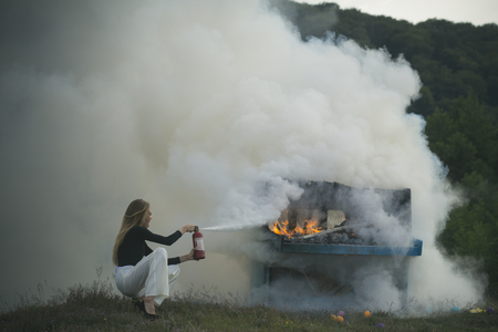 Fire and smoke on grunge instrument. fire and white smoke at burning piano and girl firefighter.