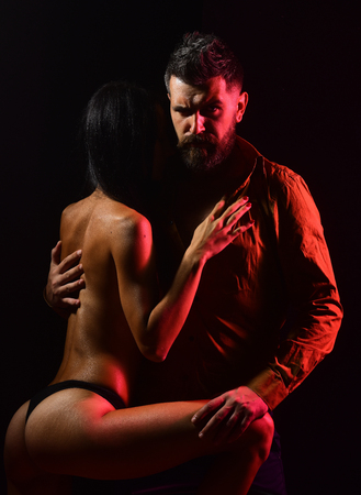 sexy topless woman hugging a bearded stern looking man