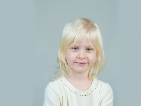 Little girl with young tender skin. Fashion style and beauty look. Kid with blonde hair. Childhood and happiness of innocent girl. Child with happy face and blond hair on grey background.