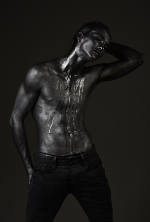 Fashion and masculinity concept. Man with nude torso covered with shimmering silver paint, dark background. Guy posing with confident expression. Macho with streams of sweat or paint on naked chest.