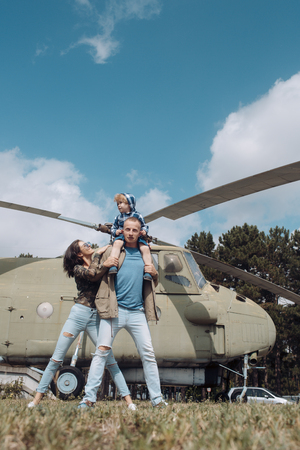 Happy family spend time together, on excursion, helicopter on background, sunny day. Family leisure concept. Mother and father and child walking in aviation museum outdoors. Dad carries son on neck.