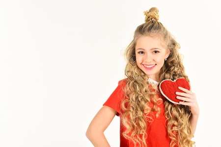 beautiful school age girl wearing red holding heart that says Happy Valentines Day, copy space