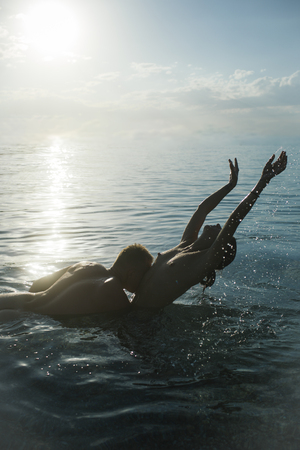 Wet lady with nude breasts and lover swimming in sea at sunrise. Girl naked with macho makes love. Honeymoon concept. Man full of desire kisses womans belly in sea. Couple in love swim naked in ocean.