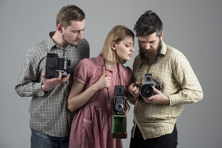 Men, woman on concentrated faces looks at camera, grey background. Company of busy photographers with old cameras, filming, working. Men in checkered clothes, retro style. Vintage photography concept.