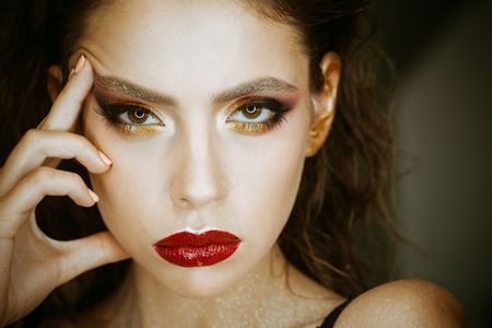 Woman with young skin face, skincare. Woman with bright makeup and red lips, beauty. Beauty model with glamour look, makeup. Skincare, cosmetics and visage. Fashion girl with curly hair, hairstyle.