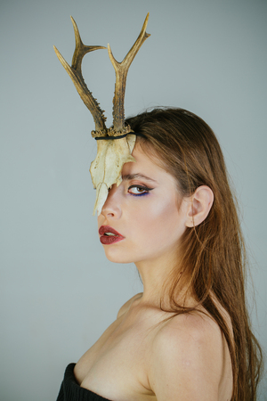 dark fantasy creature elf on halloween in skull woman with makeup and antlers fashion